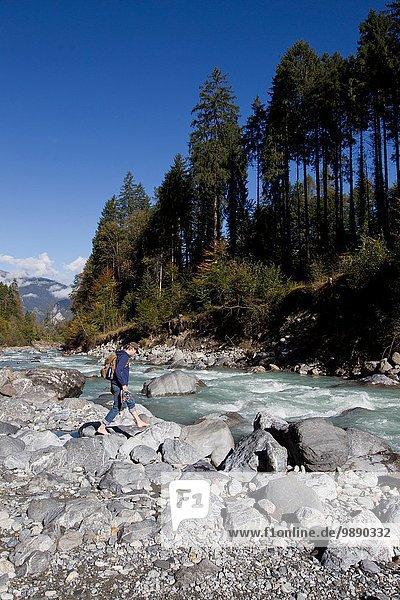 Male hiker walking on river rocks  Grindelwald  Switzerland