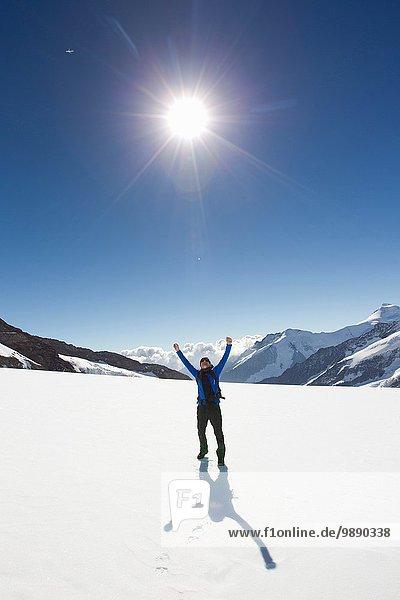 Male hiker celebrating in snow covered landscape  Jungfrauchjoch  Grindelwald  Switzerland