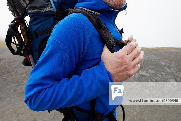 Close up of male hiker carrying backpack  Kleine Scheidegg  Grindelwald  Switzerland