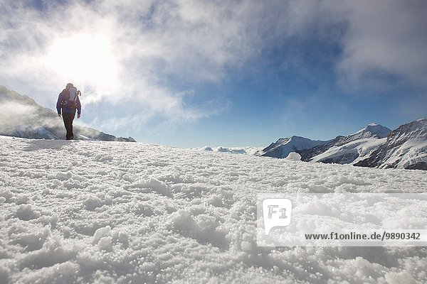 Low angle view of male hiker in snow covered landscape  Jungfrauchjoch  Grindelwald  Switzerland