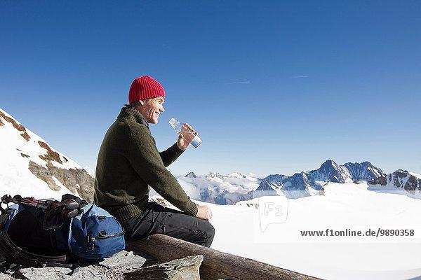 Male hiker drinking water on viewing platform  Jungfrauchjoch  Grindelwald  Switzerland