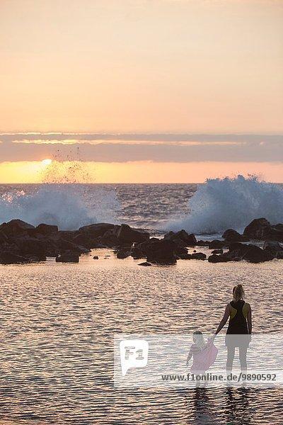 Silhouettiertes weibliches Kleinkind und Mutter beim Paddeln im Meer mit Blick auf Wellen  Kona  Hawaii  USA