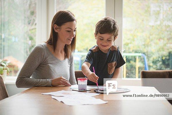 Junge lächelt mit Mutter und malt auf Papier am Tisch im Wohnzimmer.