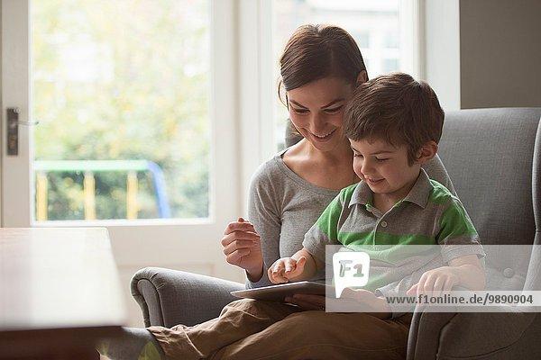 Junge sitzt auf dem Schoß der Mutter und benutzt ein digitales Tablett.