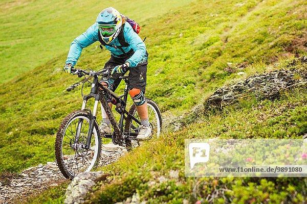 Junge Mountainbikerin beim Radfahren am Hang