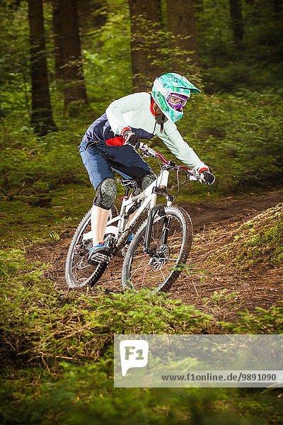 Junge Frau beim Downhill-Mountainbiken im Wald