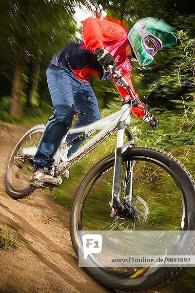 Nahaufnahme einer jungen Frau beim Downhill-Mountainbiken im Wald