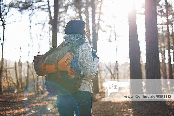 Rückansicht der reifen Frau beim Wandern im Wald