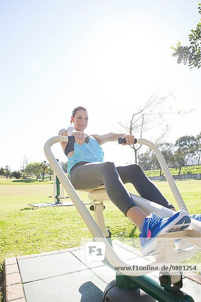 Mid adult woman in park training on rowing machine