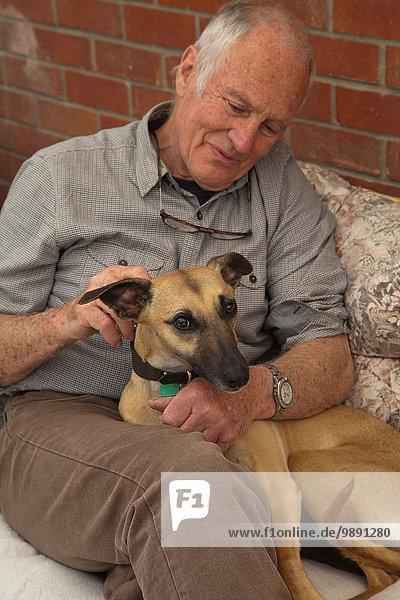 Älterer Mann  sitzend  streichelnder Hund