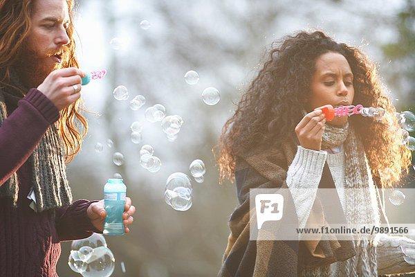 Paar blasende Seifenblasen auf dem Land