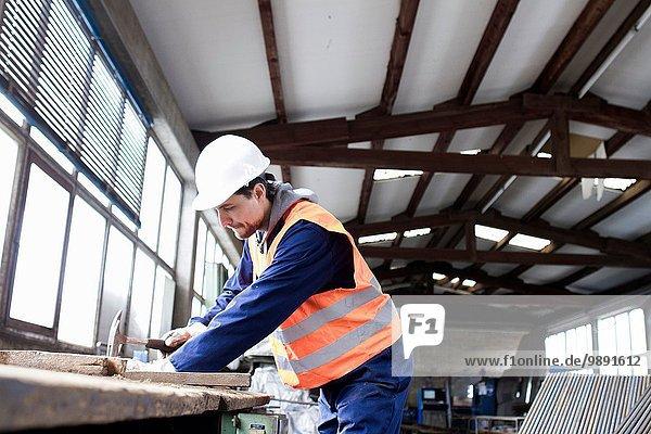 Fabrikarbeiter beim Hämmern auf der Werkbank im Betonstahlwerk