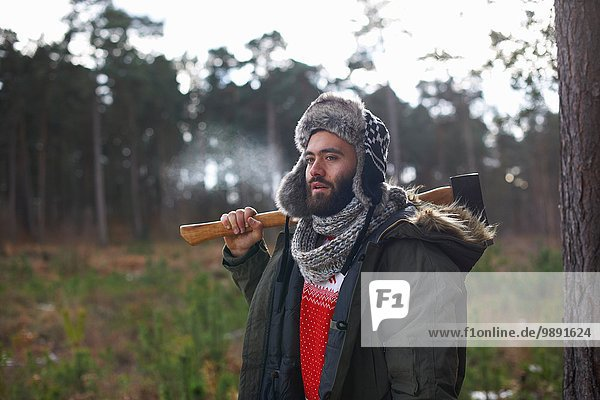 Young man carrying axe over his shoulder in forest