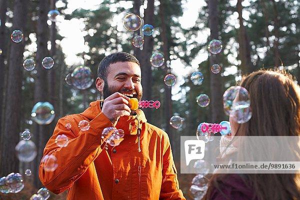 Junges Paar bläst Blasen zusammen im Wald
