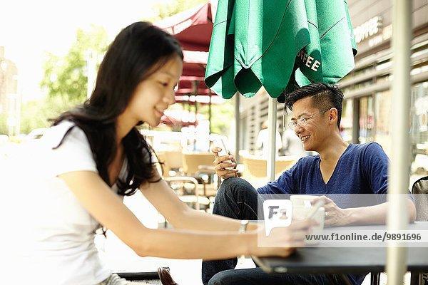 Touristenpaar im Straßencafé beim Lesen von Smartphones  The Bund  Shanghai  China