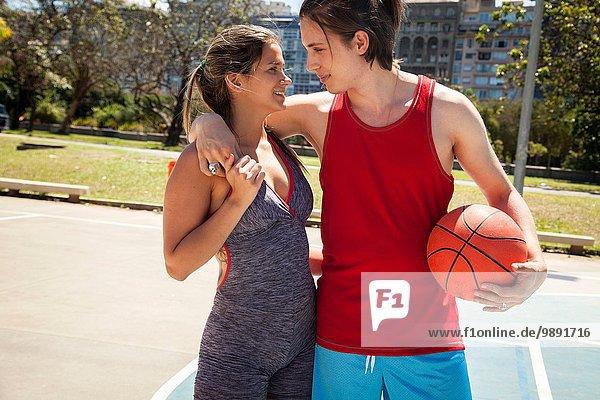 Junges Paar auf dem Basketballplatz