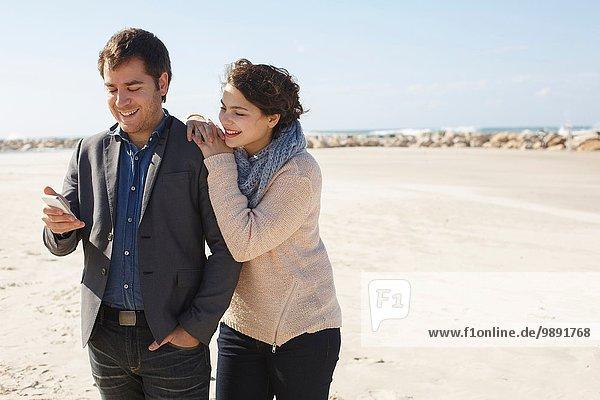 Junges Paar beim Lesen von Smartphone-Texten am Strand  Tel Aviv  Israel