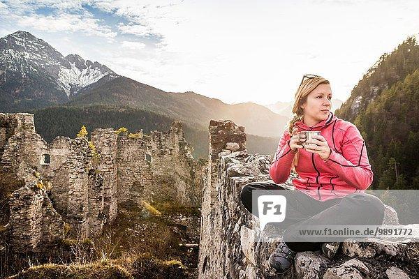 Junge Frau trinkt Kaffee auf der Burgruine Ehrenberg  Reutte  Tirol  Österreich