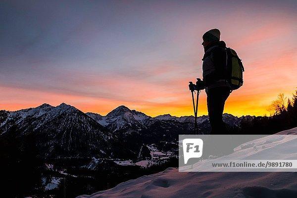 Junge Wanderin mit Blick vom Berghang in der Abenddämmerung  Reutte  Tirol  Österreich
