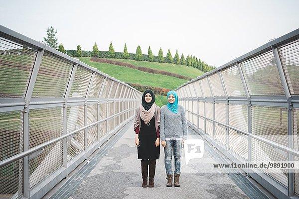 Porträt von zwei jungen Freundinnen auf der Parkfußgängerbrücke