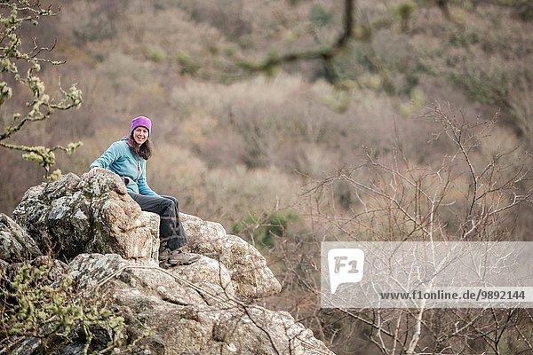 Reife Frau auf Felsen sitzend  Portrait