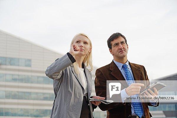 Geschäftsmann und Geschäftsfrau im Freien  hält digitale Tabletten  sieht verloren aus