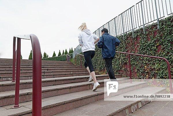 Mann und Frau laufen gemeinsam die Treppe hoch  Rückansicht
