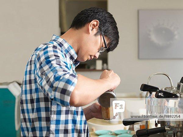 Mann arbeitet hinter der Kaffeebar