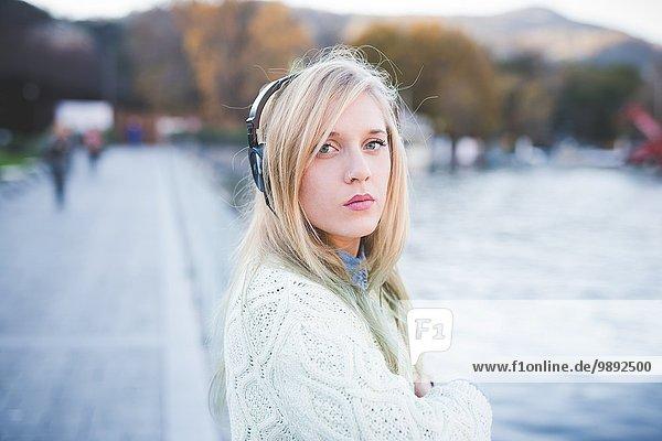 Portrait einer jungen Frau  die am Seeufer Kopfhörer hört  Como  Italien