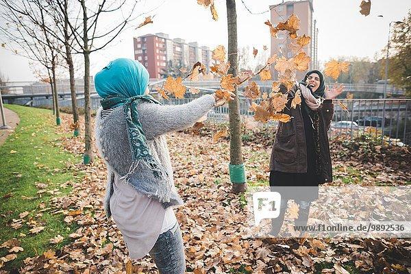 Zwei junge Frauen spielen im Park mit Herbstblättern.