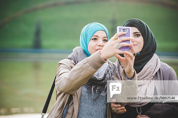 Two female friends at lakeside taking smartphone selfie