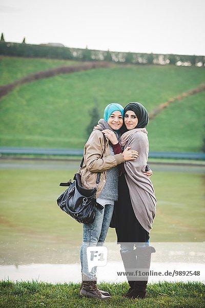 Porträt von zwei jungen Frauen  die sich am See umarmen