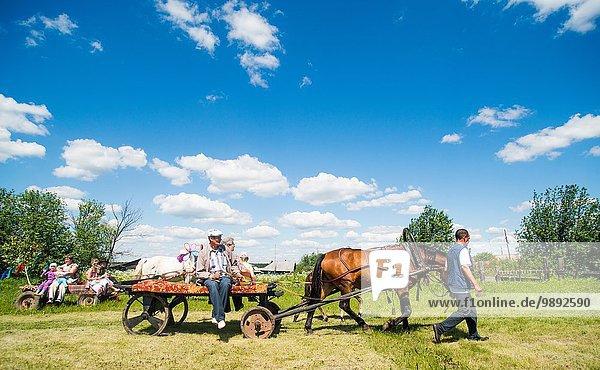 Große Familiengruppen auf Pferden und Karren im Feld  Rezh  Gebiet Swerdlowsk  Russland