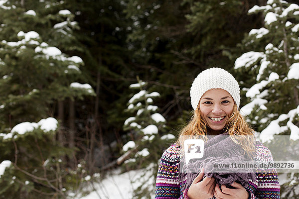 Portrait of smiling young woman in front of snow covered fir trees