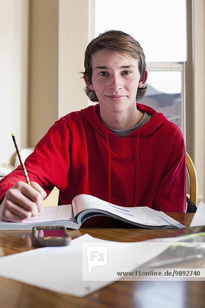 Portrait of teenage boy doing homework at dining room table