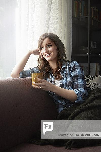 Junge Frau sitzt auf dem Sofa und trinkt Kaffee.