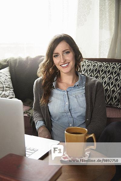 Porträt einer jungen Frau  die auf dem Boden sitzt  Kaffee trinkt und einen Laptop benutzt.