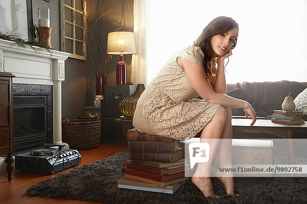 Portrait of young woman sitting on stack of books in living room