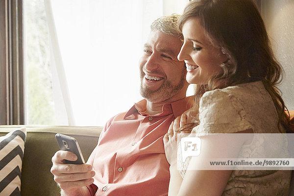 Junges Paar auf dem Wohnzimmersofa beim Lesen von Smartphone-Texten