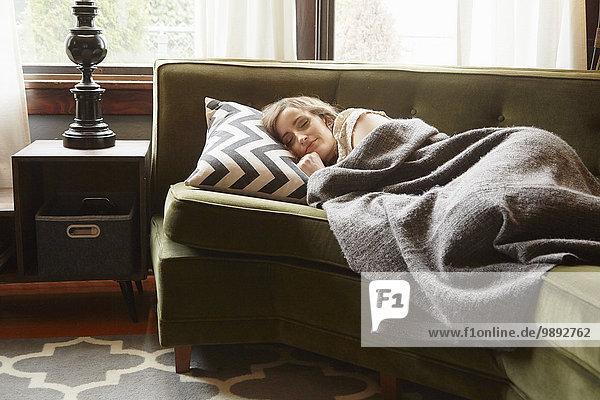 Junge Frau auf dem Wohnzimmersofa liegend in Decke gehüllt