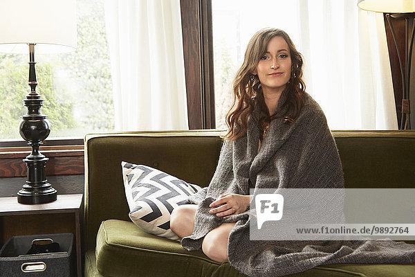 Junge Frau sitzt auf dem Wohnzimmersofa in Decke gehüllt