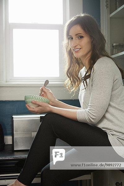 Porträt einer jungen Frau beim Frühstückscerealienessen in der Küche