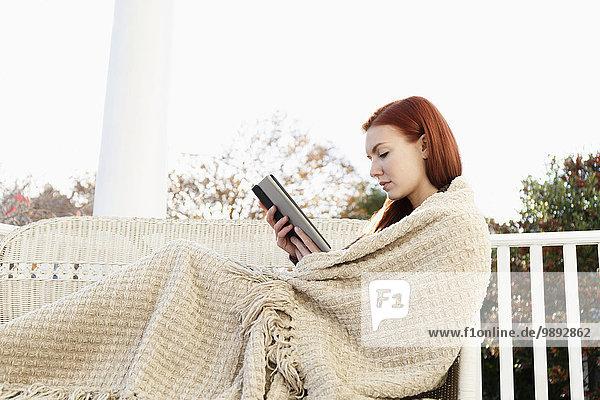 Junge Frau in eine Decke gehüllt  die auf der Veranda liest.