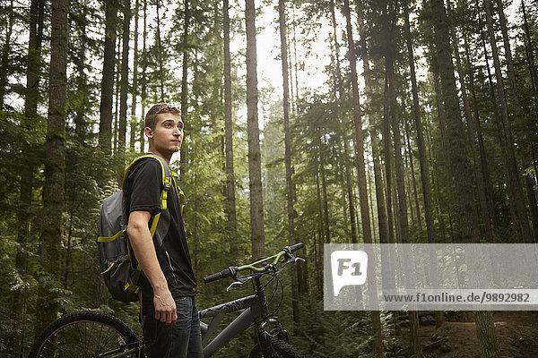 Junger Mann steht neben dem Mountainbike  im Wald