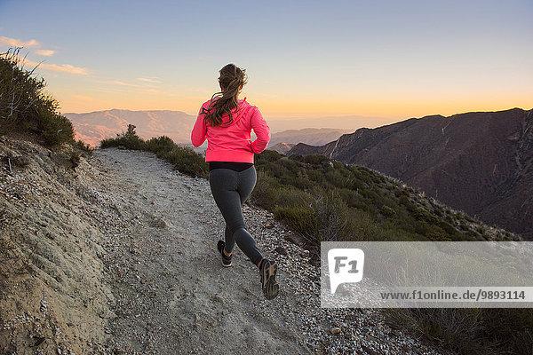Rückansicht des Trails der jungen Frau  der in der Abenddämmerung auf dem Pacific Crest Trail  Pine Valley  Kalifornien  USA  auf den Feldweg läuft.