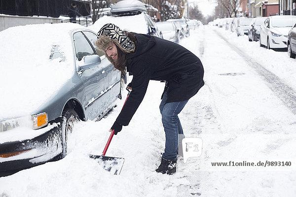 Junger Mann beim Schneeräumen mit der Schaufel