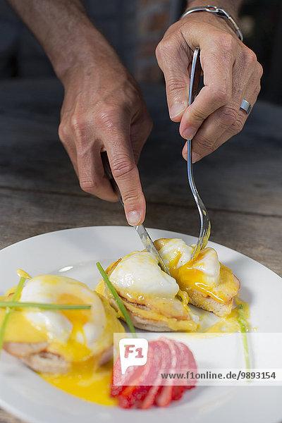 Hands of man eating eggs benedict for breakfast
