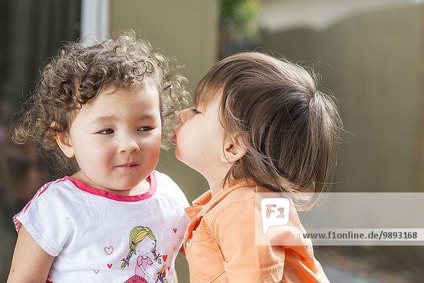 Männliches Kleinkind küssendes weibliches Kleinkind auf der Wange im Hinterhof