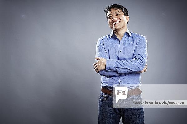 Porträt eines erwachsenen Mannes  Arme gekreuzt  lächelnd