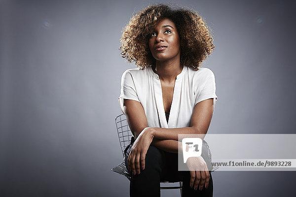 Porträt einer jungen Frau  die auf einem Stuhl sitzt und wegschaut.